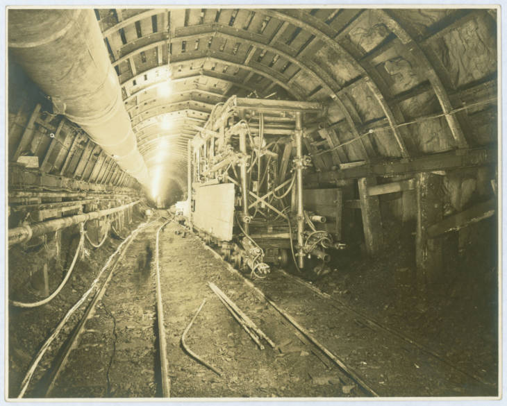 A yellow-toned monotone photo of a tunnel lined with wood planks and concrete. There is a rail track and pipes going down into the far distance. Scaffolding sits off to the side.