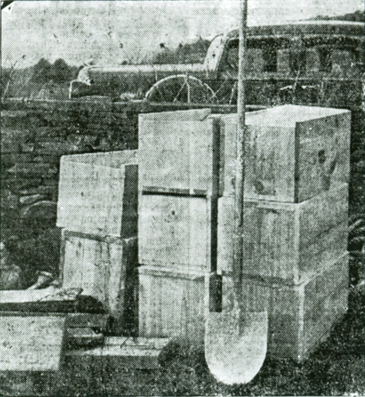 A black and white photo of a group of wood boxes stacked on top of one another and a shovel leaning against the stack.