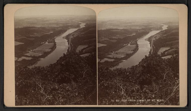 "A stereoscopic black and white photograph of a river seen from high up on a hill. Farmland surrounds the narrow-looking river. The text ""View from summit of Mt Minsi"" is typed onto the image."