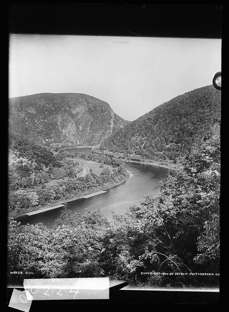 A black and white photo with a black border and tape artifacts covering some numbers. The photo shows a river curved through a mountainous valley. The photo is taken from high up on a mountain looking down.
