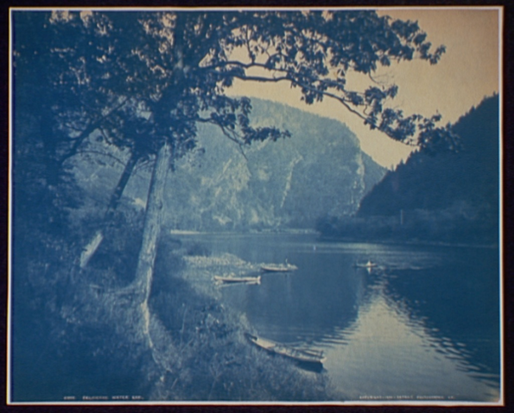 A faded color photo of a riverbank with canoes in the foreground. In the background there are two mountain cliffs hugging the curves of the river around the bend.