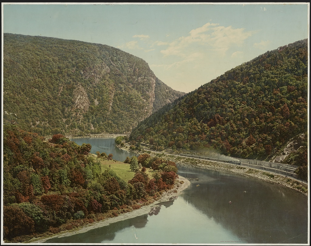 A hand-colored photo taken from up high of a river winding around two large mountains with big cliffs. A train is blowing smoke as it chugs along the riverside.