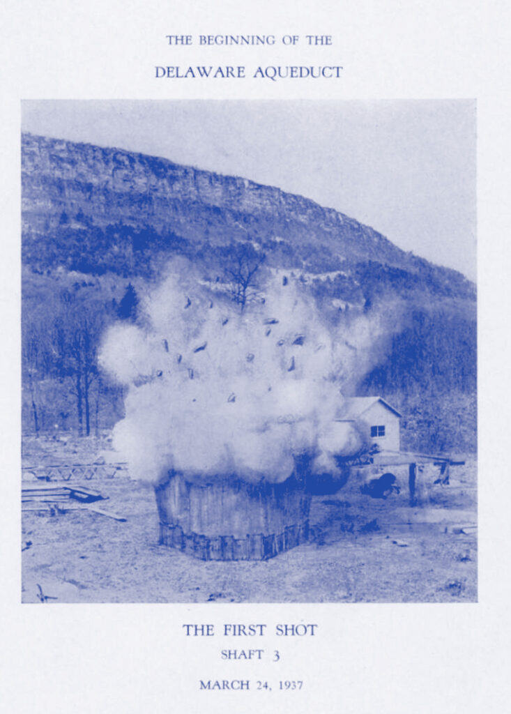 A blue toned monotone illustration with white border and text. The drawing is well or tunnel sticking out from the ground, with a plume of smoke and explosion debris flying in the air from it. There is a mountain ridge in the background.