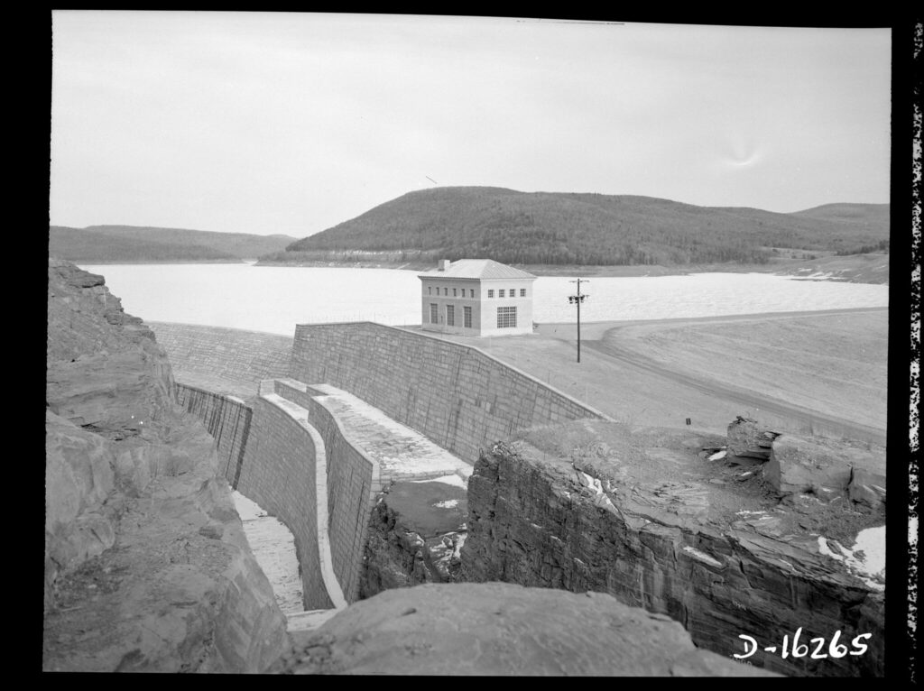 A black and white photo of rocky cliffs in the foreground surrounding a dam wall and brick building that overlooks the reservoir. In the background sits a mountainous horizon.