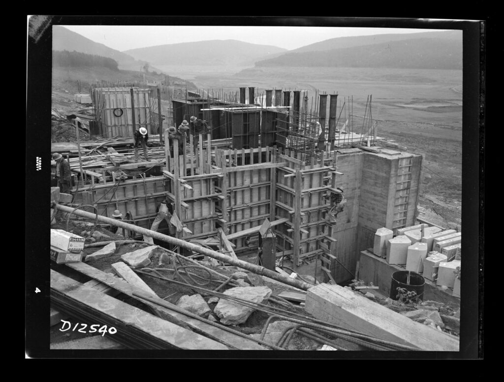 A black and white photo of a construction site on the side of a hill looking down on an empty valley. There are structures being prepped to pour concrete into.