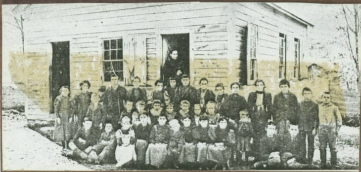 A black and white photo of a class of children and their teacher standing in front of a wood building.