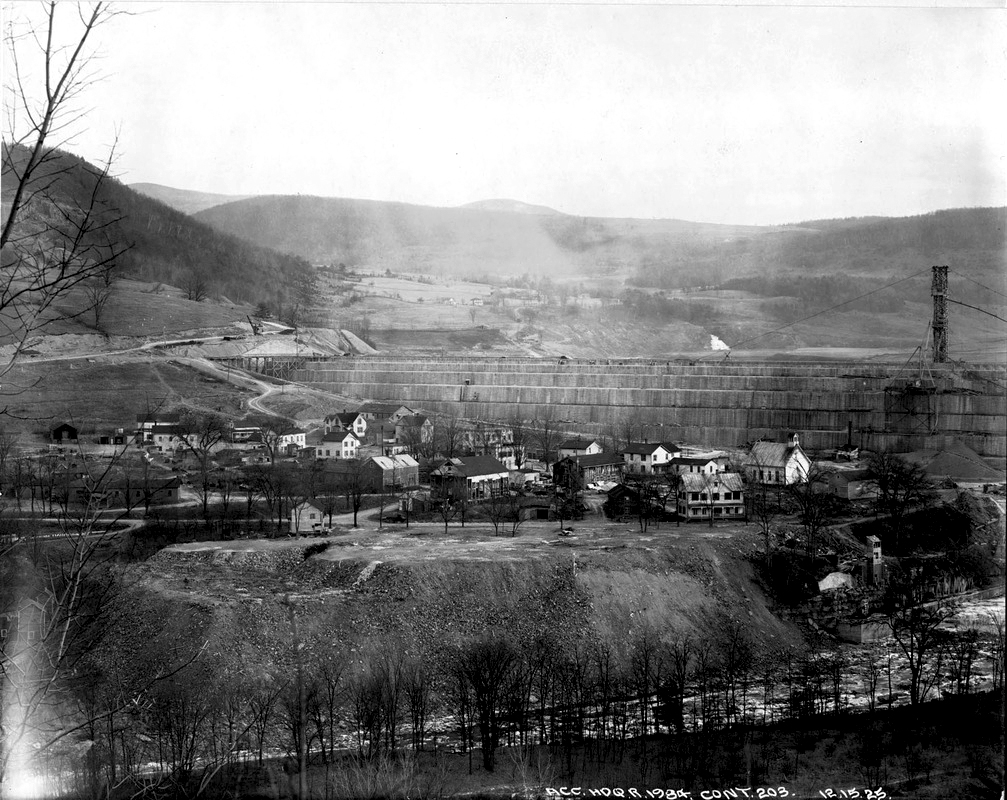 A black and white photo of a valley landscape. In the foreground there is about 17 homes sitting on a cliff above a stream below, and looming above the town is a large dam wall under construction. There are mountains in the background.
