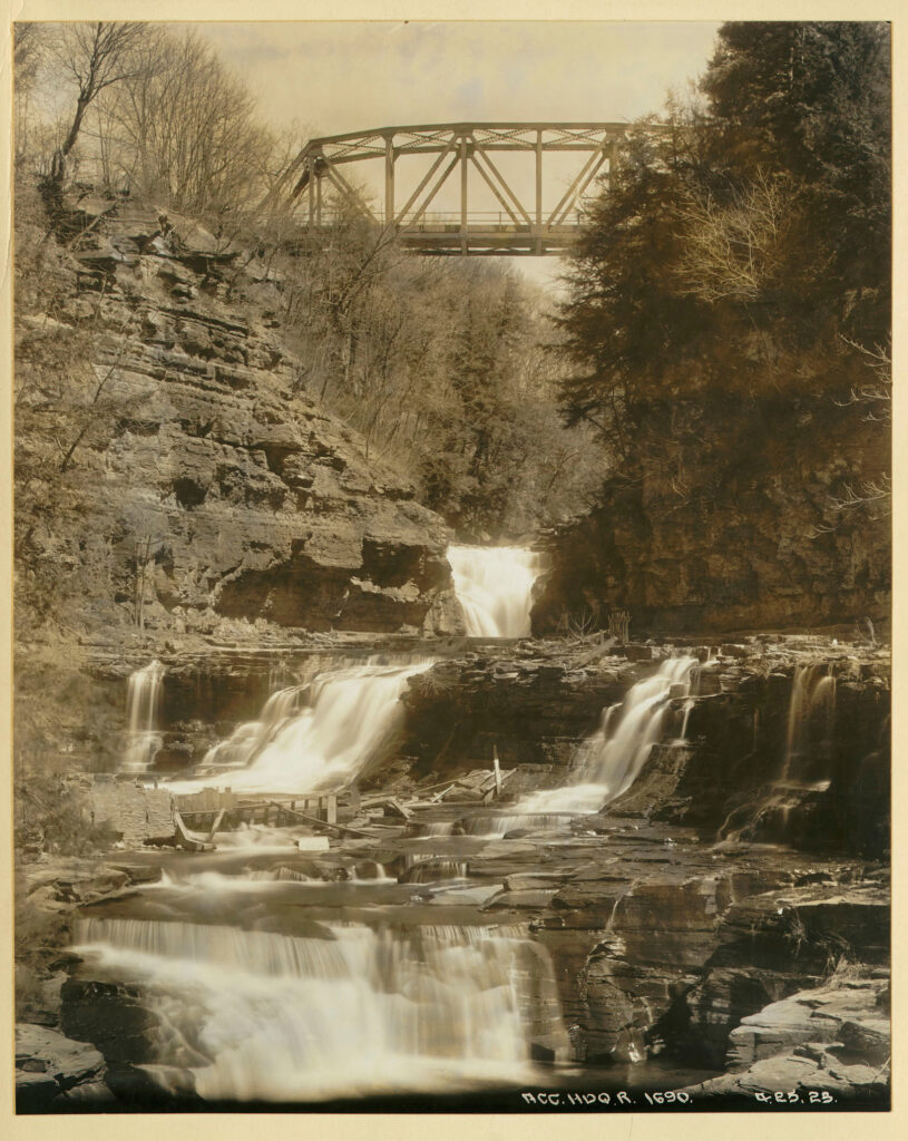 A black and white photo of a picturesque water fall underneath a small steel bridge.