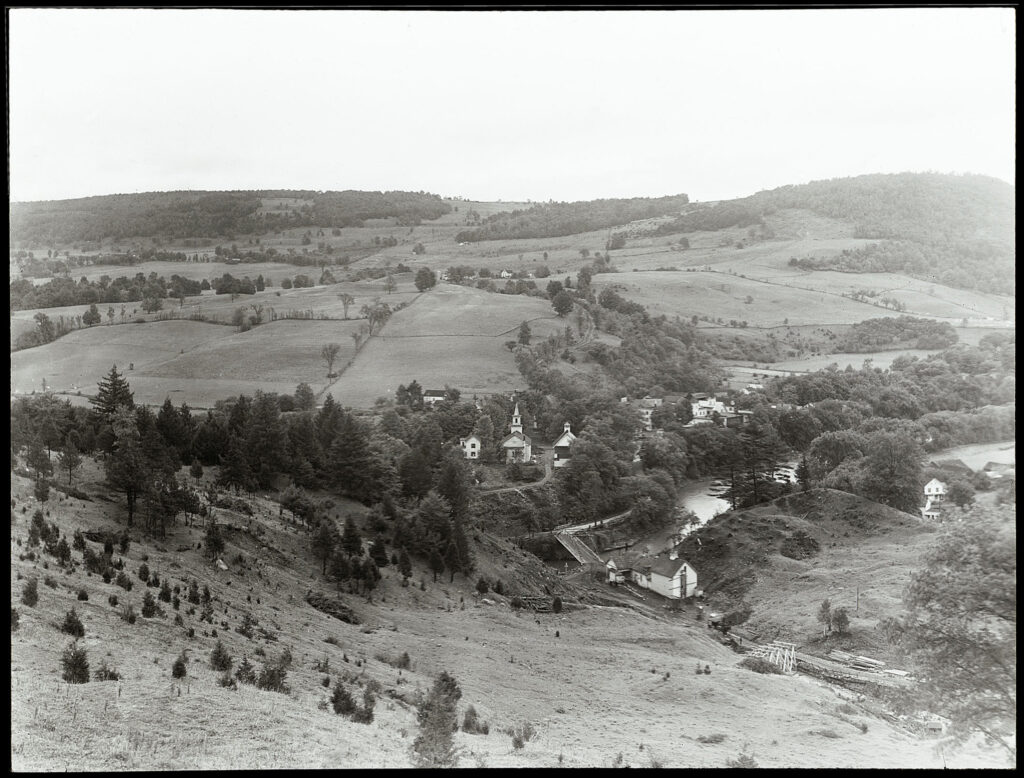 A black and white photo of an rural landscape with rolling hills. In the middle of the photo is a small village cloaked in trees. There is a church visible in the center. A creek runs below the town and farmland stretches into the background.