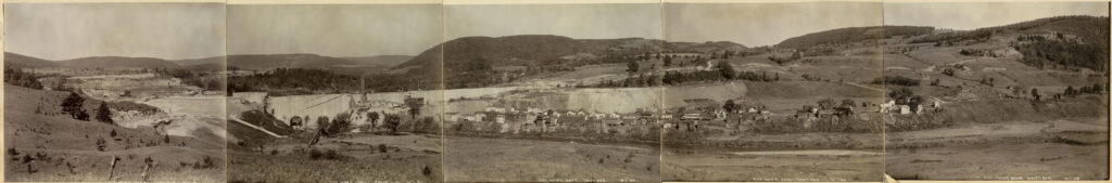 A black and white panoramic photo of a rural valley landscape with a small village situated at the base of a large dam wall under construction.