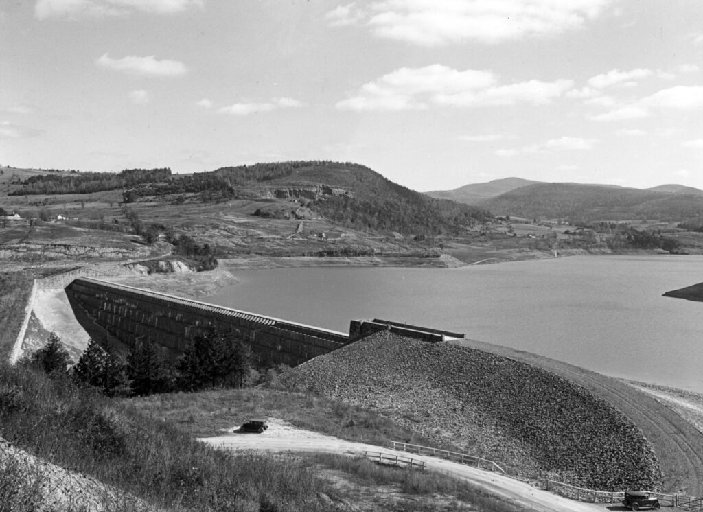 A black and white photo taken from high on a hill above a dam and dam wall. There are a couple of old cars parked on the dirt road in the foreground. Mountains and valleys stretch into the background.