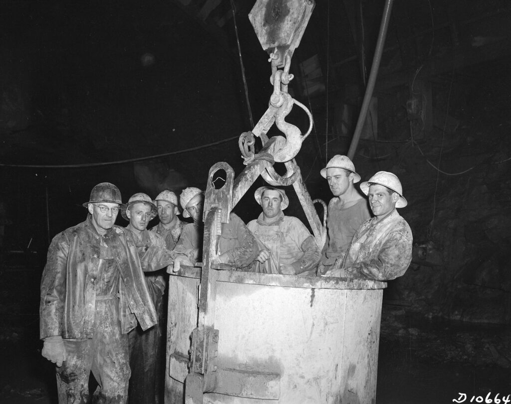 A black and white photo of a group of workers in hard hats against a dark background. Four are in a steel tub attached at the top to a crane hook.