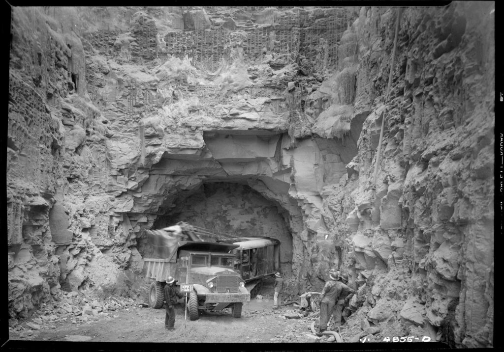 A black and white photo from the bottom of an excavated site. Rock has been blasted and carved away to make a large passage leading into the entrance of a tunnel. There is a couple of trucks at the entrance to the tunnel.