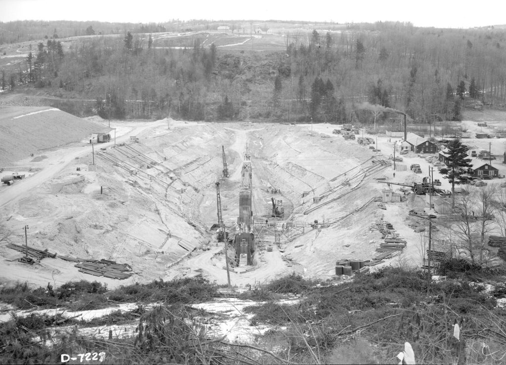 A black and white photo looking down onto an excavation site. It looks like a slit in the earth has been cut.
