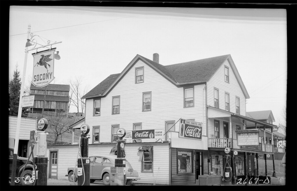 A black and white photo of a white three story wood building with gas pumps outside and coca cola advertisement signs affixed to the outside of the building.