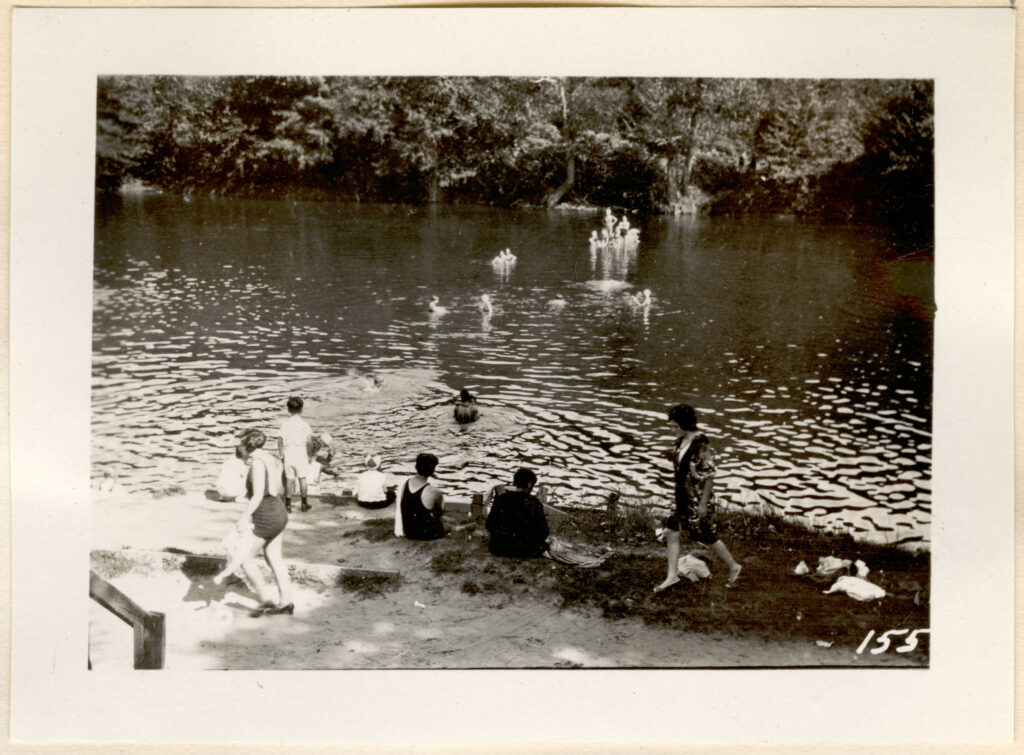 A black and white photo of a rivers edge with a group of boys in and out of the water.