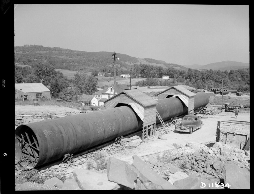 A black and white photo of a long steel tube with two wood sheds straddling it, as if the tube is a railway car going through a tunnel