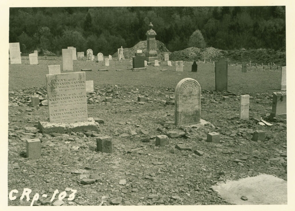 A black and white photo of tombstones in a cemetary.