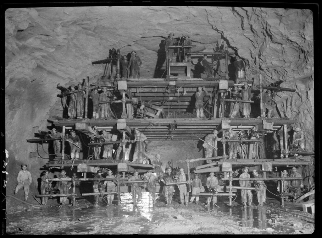 A black and white photo taken inside of a tunnel under construction with workers posing on four stories of scaffolding.