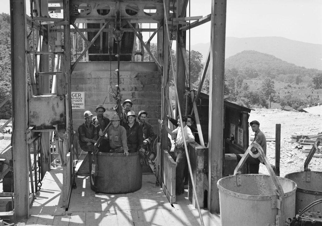 A black and white photo of 6 men in hard hats sitting in a metal bucket that is staged on a crane platform. In the background is a hilly landscape.