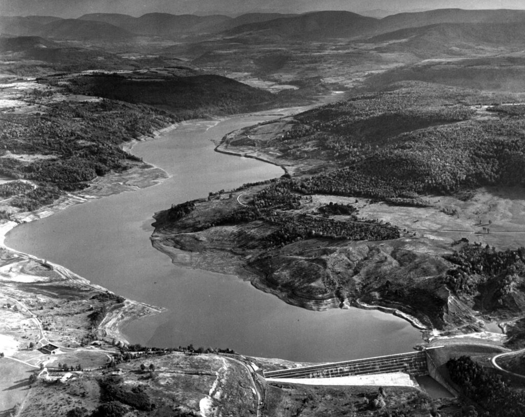 A black and white aerial photo of Schoharie dam including the dam wall in the foreground, and mountains and valleys in the background.
