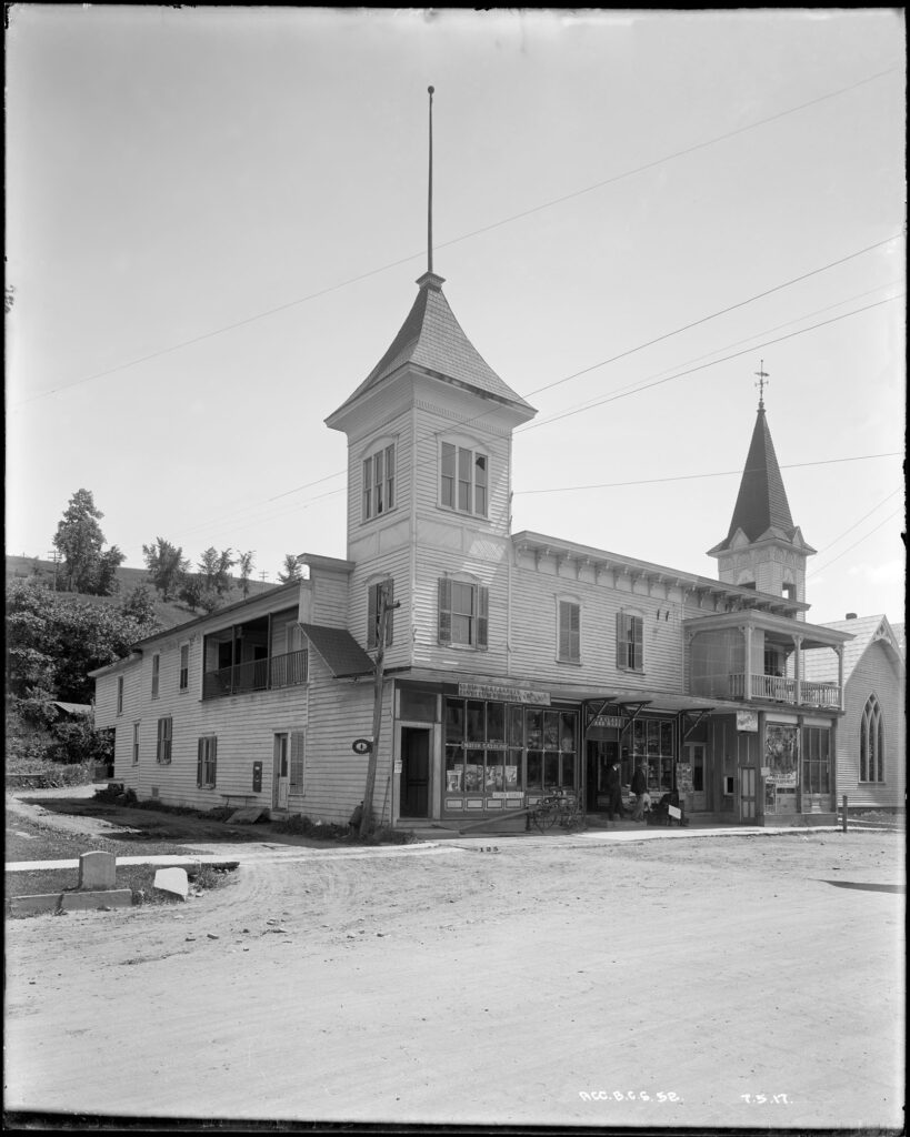 A black and white photo of a white building with wooden siding and two large turrets rising above the 2nd floor on each corner facing the street. There is a church next door on the far side. There are commercial businesses and window displays on the ground floor.