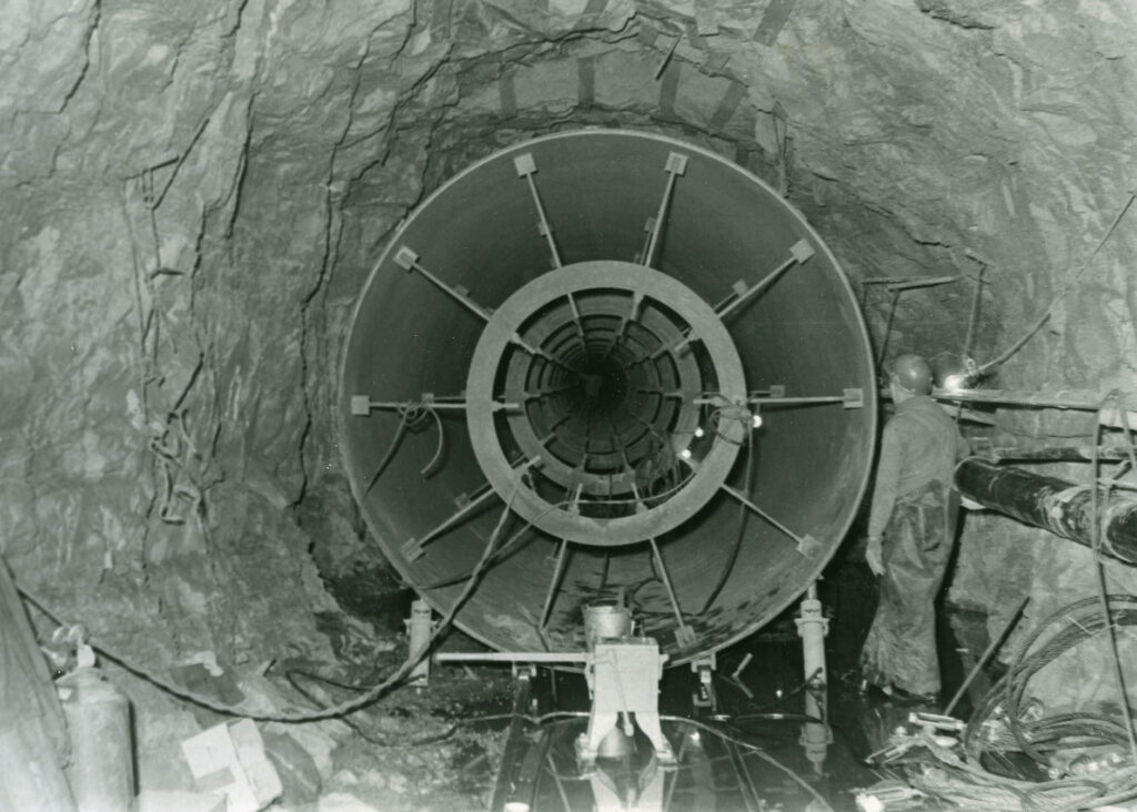 A black and white rock tunnel with a metal tube that fits into the tunnel with just a couple of feet to spare. A man in a hard hat is looking at the tunnel, which is twice his size.