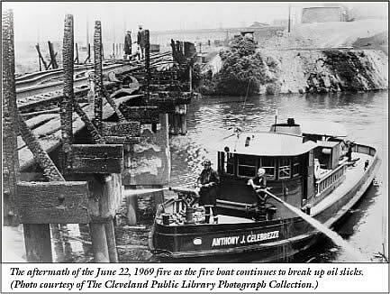 A black and white photo of a jetty on a river. A small boat is in the foreground with two men blasting water out of water canons towards the charred wood jetty. In the background black smoke rises from a charred land mass.