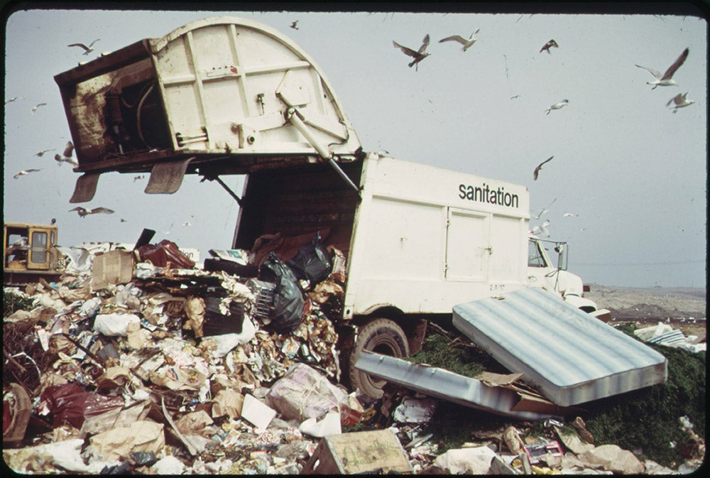 """A color photo/film still of a white garbage truck unloading a load of garbage into a landfill. Seagulls fly overhead. The truck is marked """"sanitation"""" on the side."""