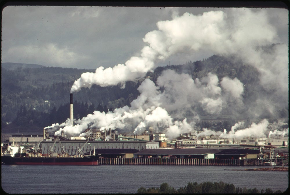 A film still of a factory situated on a waterfront with mountains in the background. Smoke coming from multiple smoke stacks envelops the landscape and predominates the photo frame.