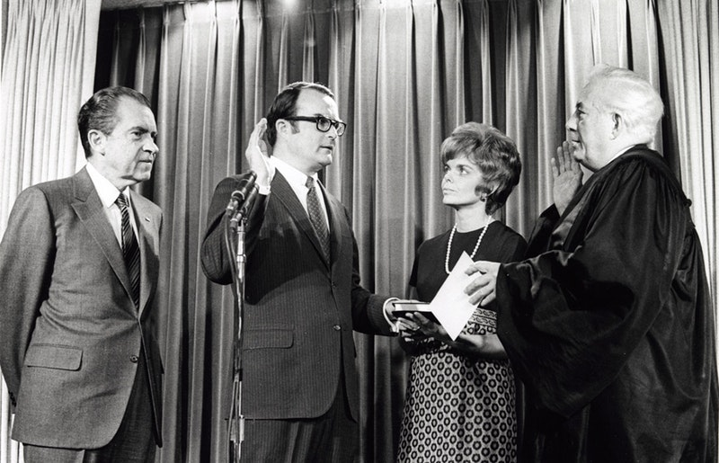 A black and white photo of three men and one woman. President Nixon stands aside looking at the man beside him who has his left hand on a bible and is holding his right hand up signaling he is swearing on the bible. A man in a black robe officiates as a woman in a short '60s haircut looks on.