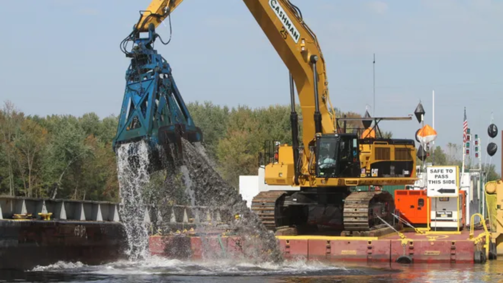 A tractor with a crane arm lifts a load of load of watery grey debris out of a body of water.