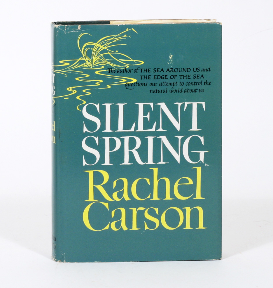 """A photo of a hardback book standing against a white background. The book cover has a blue-green solid background with a yellow wavy graphic resembling light refractions on water. The book title and author: Silent Spring, Rachel Carson"""" are written in bold text, filling most of the space."""