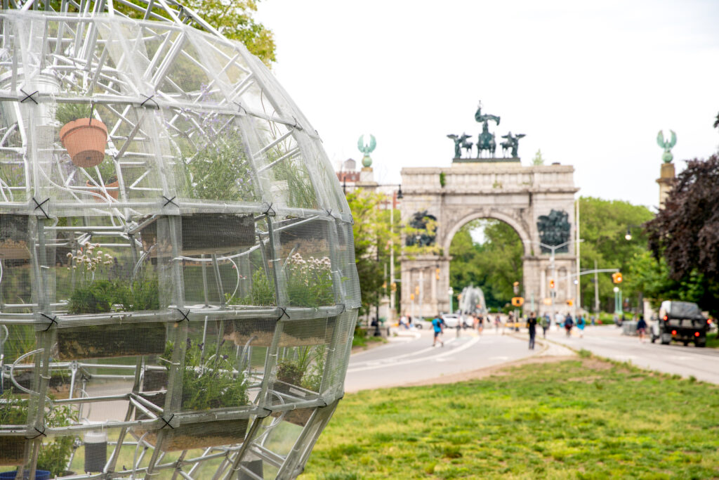 A quarter of a sculpture peeks out from the left side of the frame. The sculpture is a large sphere made of metal bars covered in a steel mesh skin. Inside there are clear tubs attached to the walls and skeleton of the sphere that have brown soil, rocks, and plants inside of them. In the background stands the Grand Army Plaza stone gates and a stretch of green grass in between the sculpture and the gates.