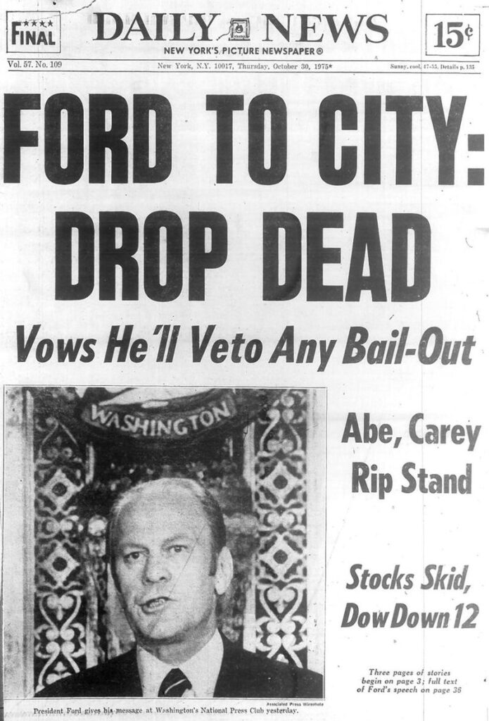 """A photo of the front page of the New York Daily Newspaper. A large headline reads """"FORD TO CITY: DROP DEAD. Vows he'll veto any bail-out. Abe, Carey Rip Stand. Stocks skid, Dow down 12"""" with a photo of President Ford, with a decorative plaque behind him."""