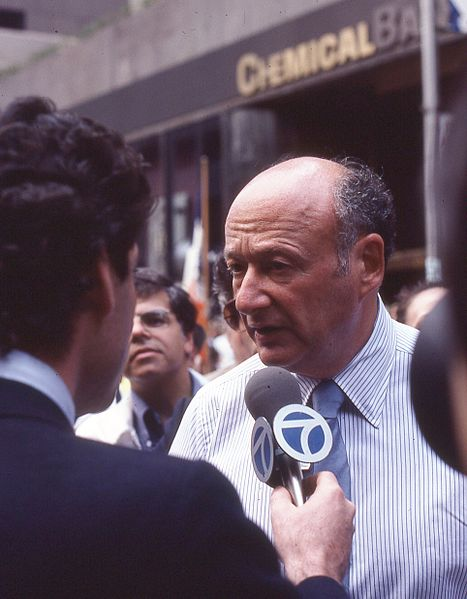 A color photo of Mayor Ed Koch on the street with a TV reporter holding a microphone in front of the Mayor's face. The Mayor is wearing a blue collared shirt and tie. He is balding with dark/grey hair.