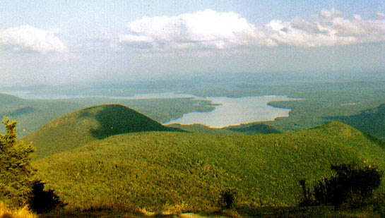 A color photo taken from up high on a mountain looking down on the Ashokan Reservoir which is surrounded by forest and mountains. The mountains in the foreground have dark patches on them caused by cloud cover.