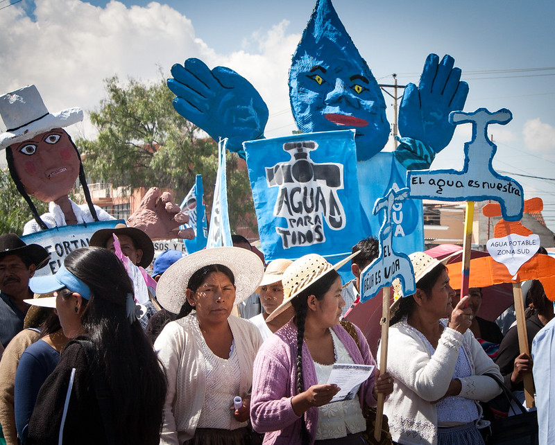 """A color photo of a group of mostly women outside at a parade. There are signs in Spanish saying """"Agua Para Todos"""" and puppets of water droplets and Chilean women with hats."""