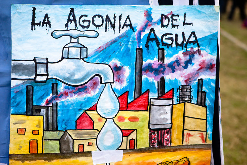 """A photo of a hand painted protest sign that shows a landscape with a city backed by a mountain. A tap with water droplets is placed in front and center. The words """"La Agonia Del Agua"""" are written on top."""