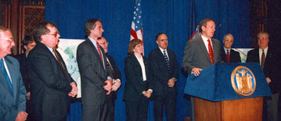 A color photo of eight men and one woman standing watching a man at a podium. They are standing with their hands clasped in front of them in front of a blue curtain. They are all wearing suits.